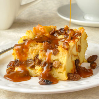 Close up photo of one serving of Rum Raisin Bread Pudding with sauce being poured on