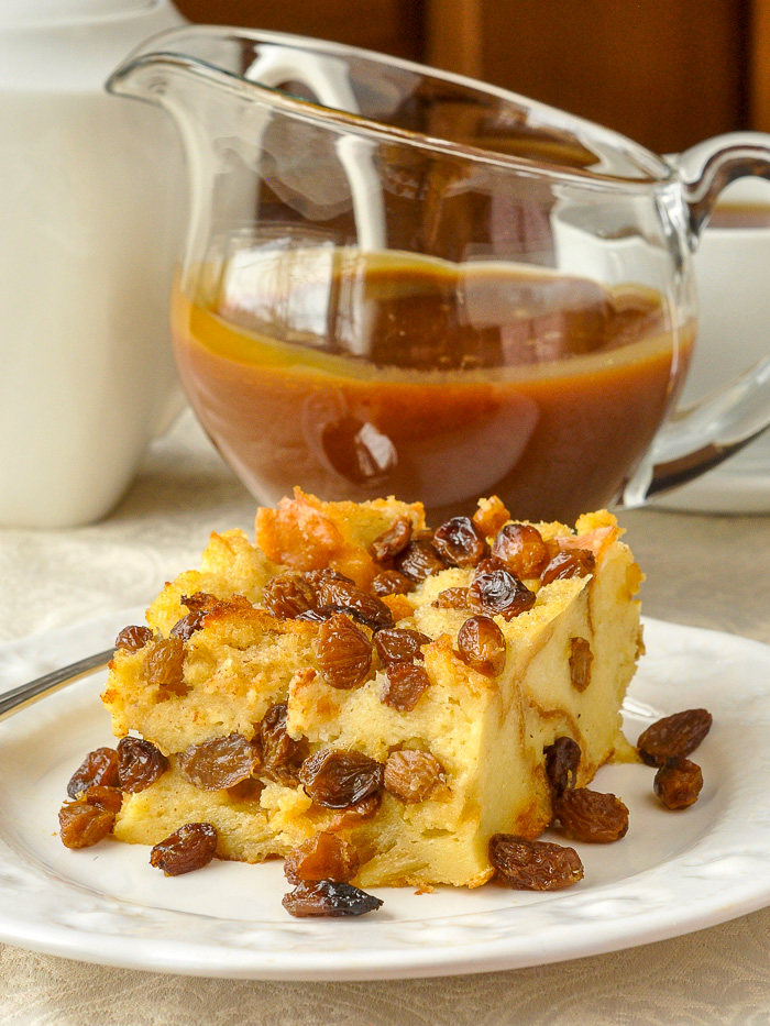 Rum Raisin Bread Pudding on a white plate pictured with rum and butter sauce in background