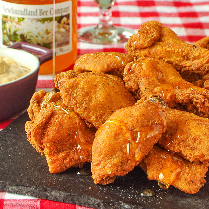 Close up photo of Southern Fried Wings being drizzled in honey