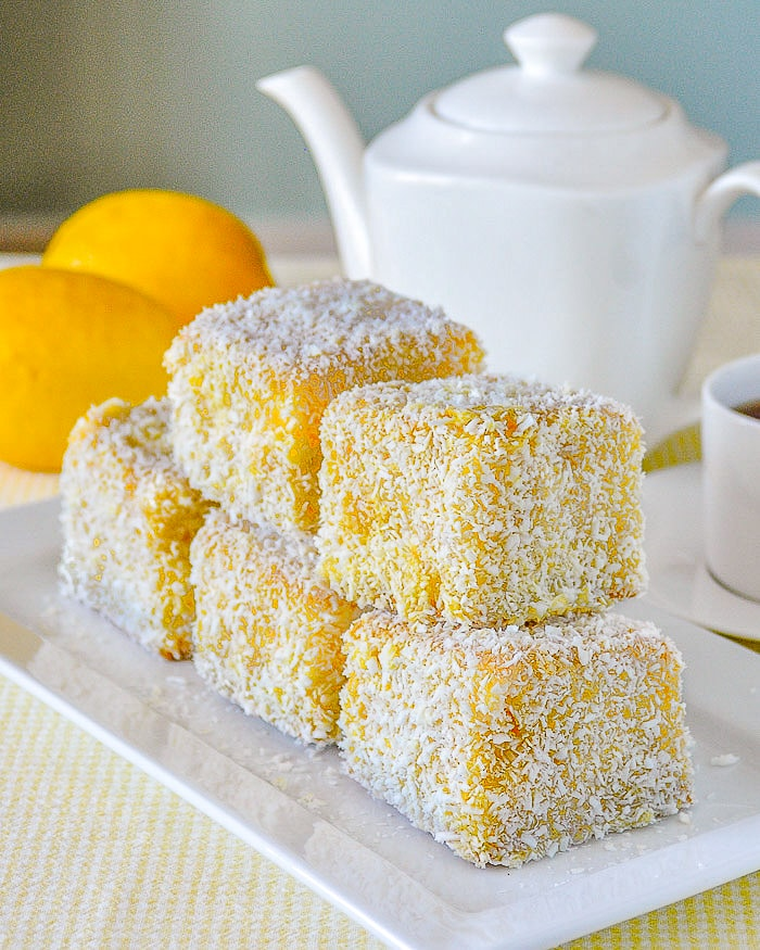 Lemon Lamingtons stacked on white serving plate.