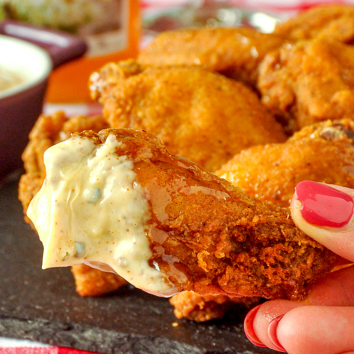 Southern Fried Wings Close up photo of one wing dipped in the aioli