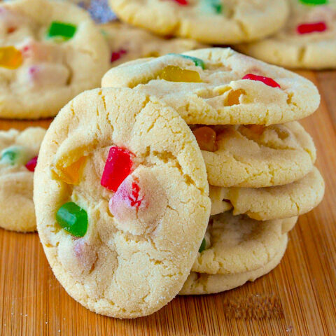 Close up photo of Gumdrop Sugar Cookies stacked on a wooden cutting board