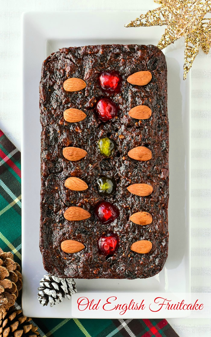 Old English fruitcake overhead photo of baked loaf cake on a rectangular white platter with title text added for Pinterest.