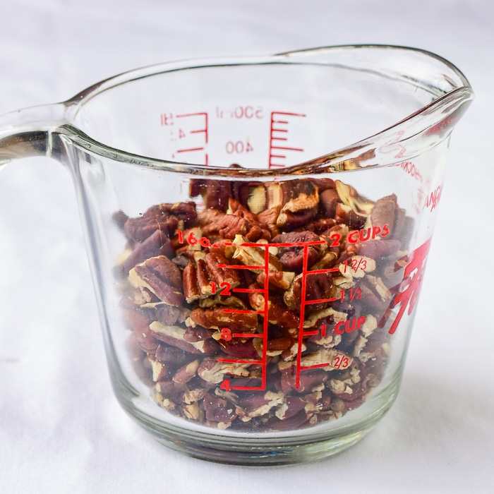 Pecan pieces in a clear glass measuring cup