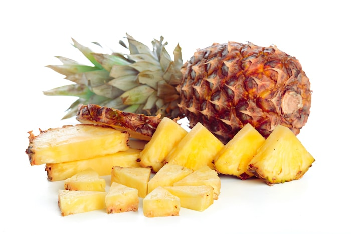 Fresh Golden Pineapple cut in pieces on white background.