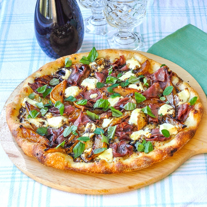 Caramelized Pear Prosciutto Pizza on a wooden peel with wine and glasses in background