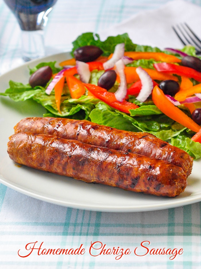 Homemade Chorizo Sausage shown with salad on a white plate with title text added for Pinterest