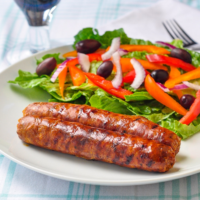 Homemade Chorizo Sausage shown with salad on a white plate