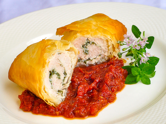 Phyllo Chicken Herb Roulade with Roasted Tomato Jam shown on a white platter with flowering oregano garnish