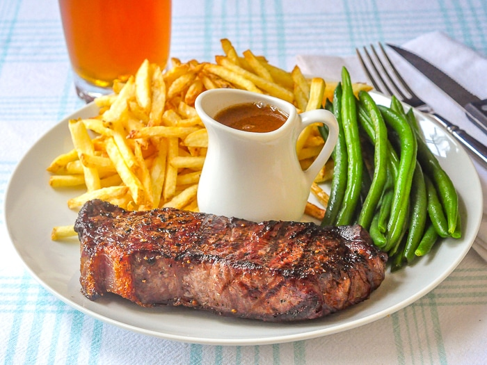 Steak Frites on a white plate with grren beans, gravy and a glass of beer in background
