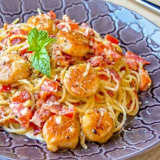 Creamy Garlic Scallop Spaghetti with Bacon close up photo of a single serving on a grey patterned plate