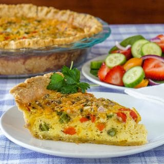 Grilled vegetable quiche, featured square image of slice on a plate with side salad in the background.