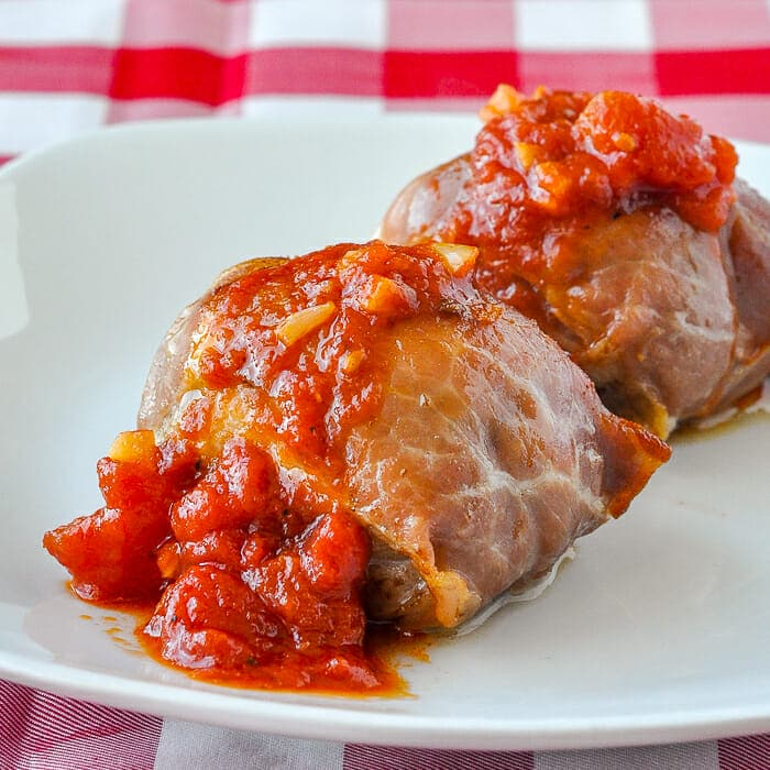 Stuffed Chicken Thighs with Prosciutto Mozzarella and Quick Tomato Sauce plated on white plate