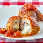 Stuffed Chicken Thighs with Prosciutto Mozzarella and Quick Tomato Sauce showing cheese melted at centre.