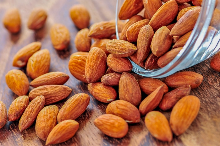 Roasted almonds spilling out of small glass bowl