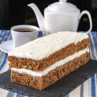 Spanish Bar Cake on a slate serving plate with coffee in the background.