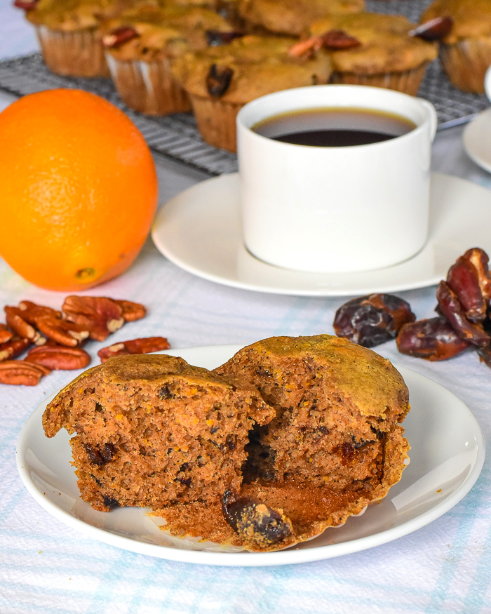 Orange Date Muffins photo of one muffin on a white plate with coffee in the background