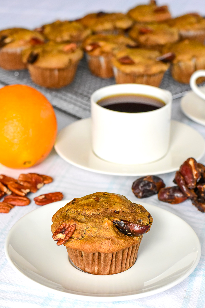 Orange Date Muffins with an orange, dates and pecans in the background