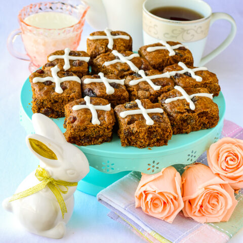 Hot Cross Molasses Raisin Tea Buns shown on a teal pedestal with Easter decorations