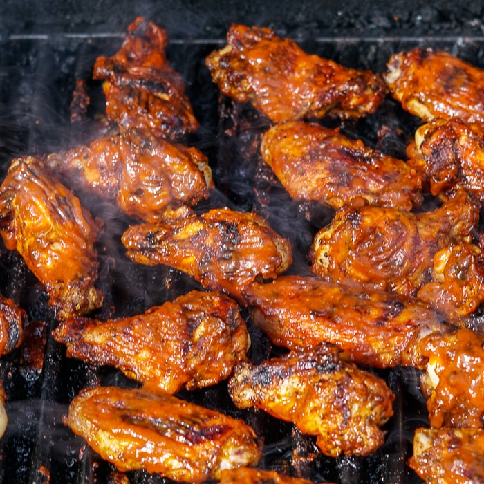 Whiskey Maple Barbecue Sauce on grilled wings being barbecued