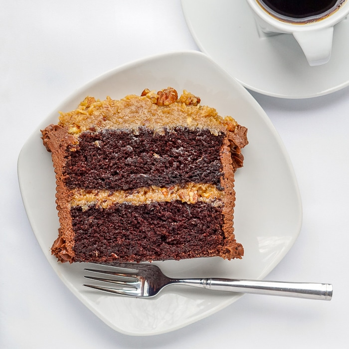 German Chocolate Cake photo of single serving on a white plate.