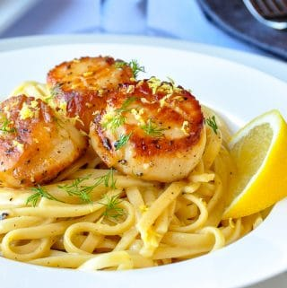 Creamy Lemon Pepper Scallops Linguine close up image in a white bowl.