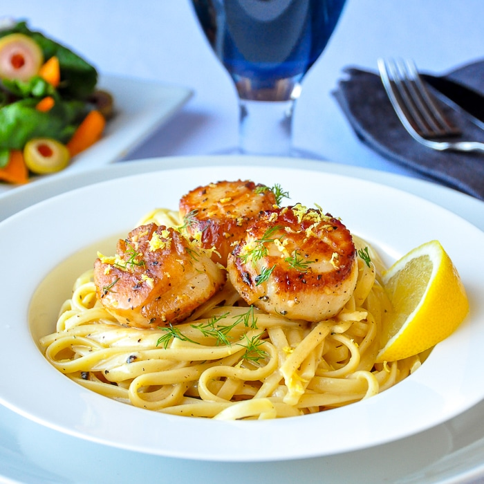 Creamy Lemon Pepper Scallops Linguine wider shot photo of entire bowl with salad in background
