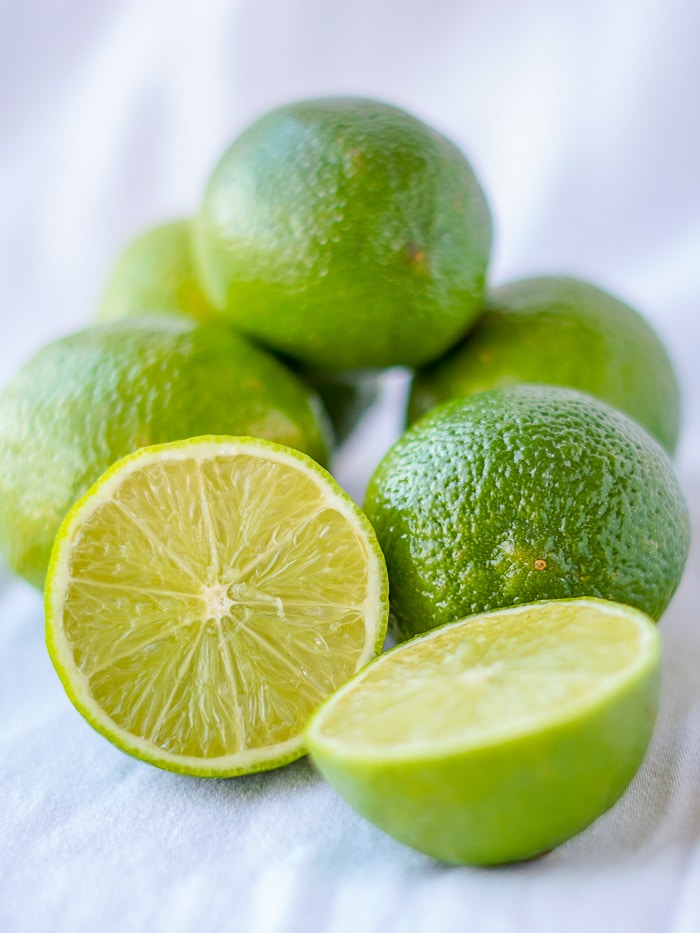 photo of limes on a white background with one cut to reveal the interior.