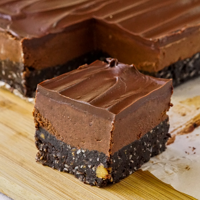 Chocolate Nanaimo Bars close up photo of singe cookie bar on a wooden cutting board