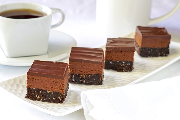 Chocolate Nanaimo Bars on a white platter with coffee in the background