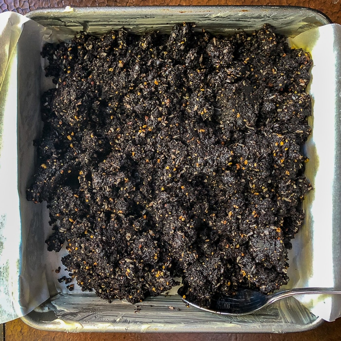 Chocolate Nanaimo Bars photo of bottom layer being pressed into pan