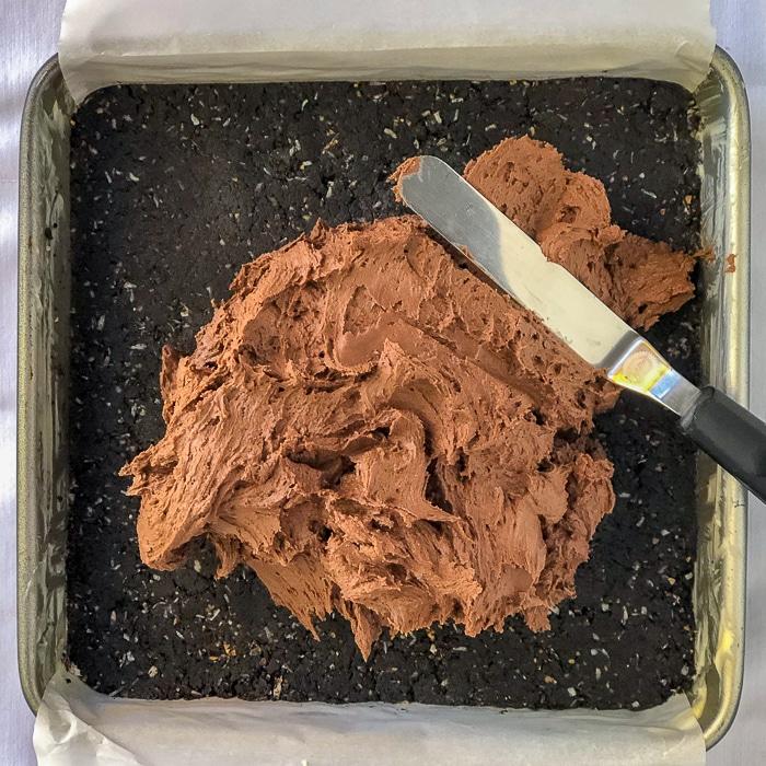 Chocolate Nanaimo Bars shown adding the centre filing