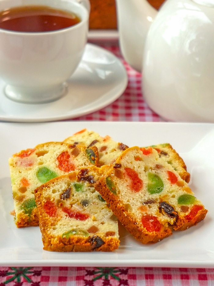Fruitcake Loaf Cake sliced and served on a white plate with tea