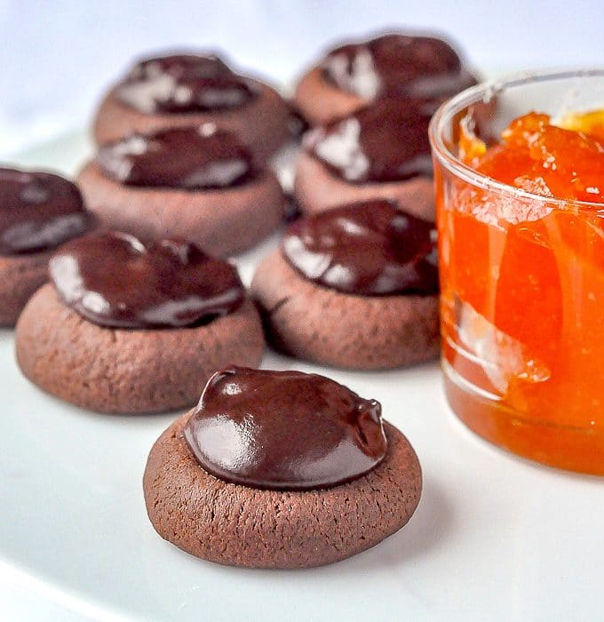 Sachertorte Cookies on a white plate beside a pot of apricot jam.