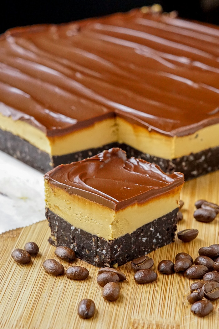 Cappuccino Nanaimo Bars with coffee beans on a wooden cutting board vertical image