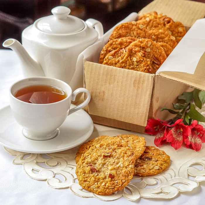 Anzac cookies in a cardboard shipping box with tea service