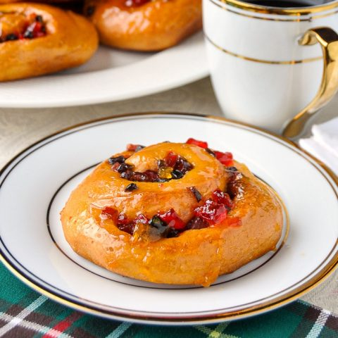 Christmas Chelsea Buns close up phopto of one bun with a gold and white coffee service