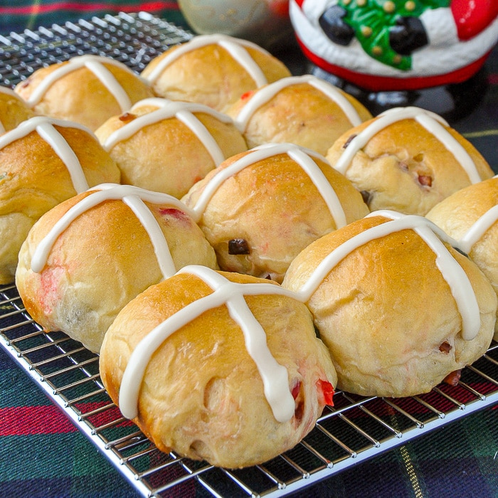 Christmas Hot Cross Buns baked and frosted sitting on a wire cooling rack