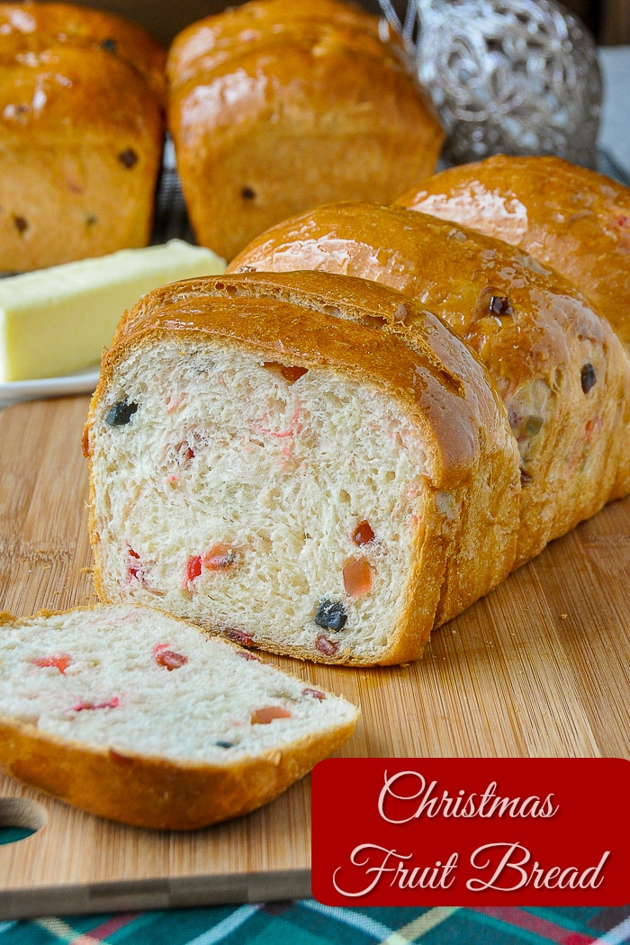 Christmas fruit bread being sliced on a wooden cutting board with title text added for Pinterest
