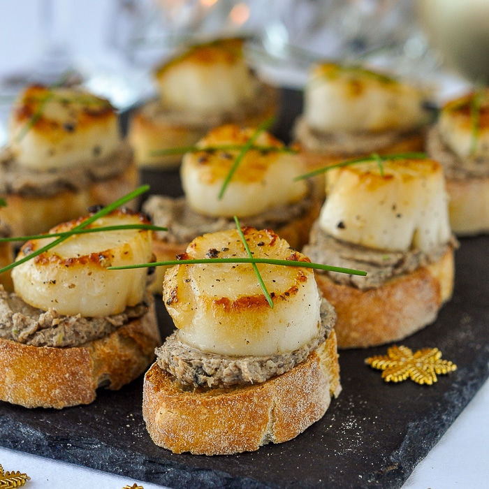 Mushroom Pâté and Seared Scallop Bruschetta shown on a slate serving platter with candles in the background
