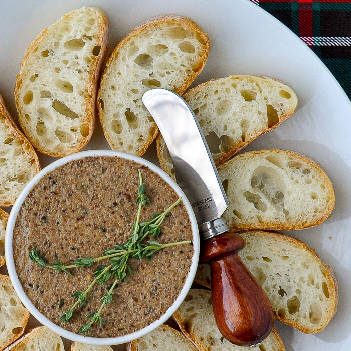 Mushroom Pâté close up featured image with thyme sprigs garnish on a white platter with sliced baguette