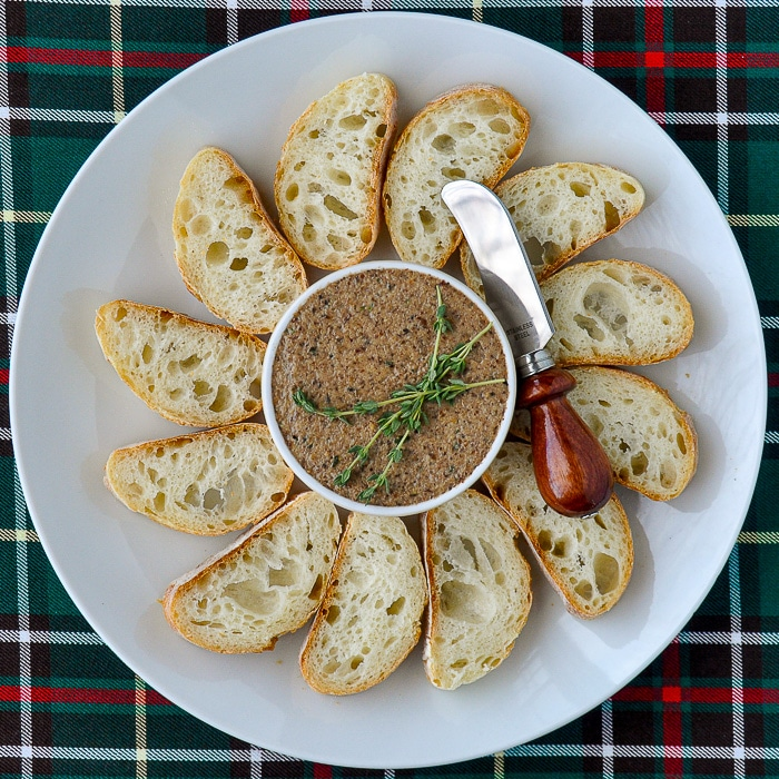 Mushroom Pâté with thyme sprigs garnish on a white platter with sliced baguette