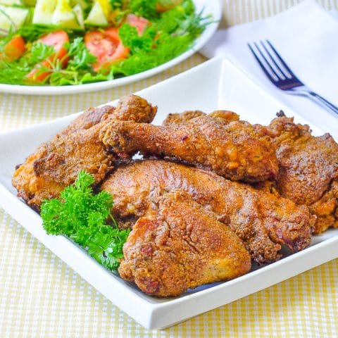 Oven Fried Chicken on a white serving platter with salad in the background.