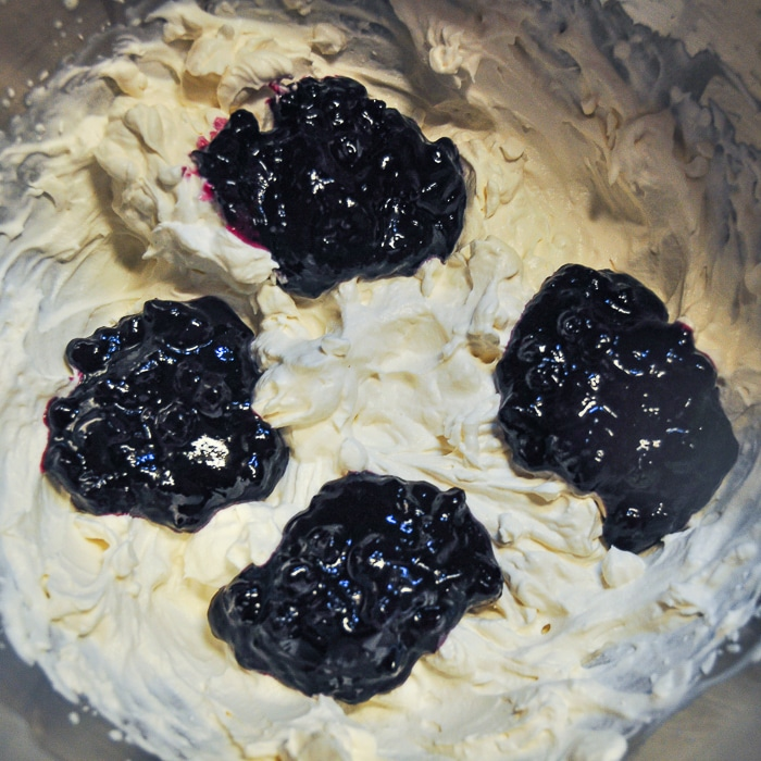 Adding the blueberry compote to the whipped cream