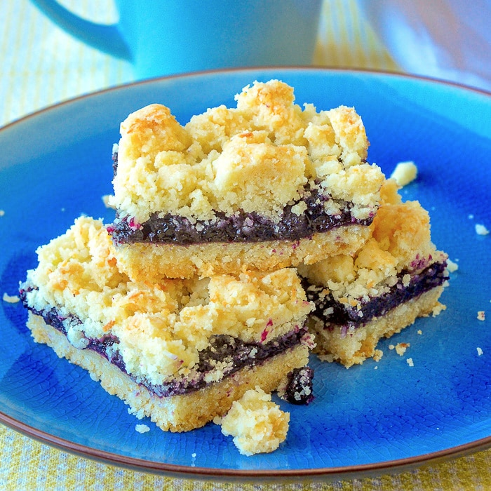 Blueberry Coconut Crumble Bars stacked on a blue serving plate