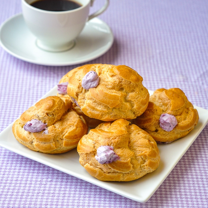 Blueberry Fool Cream Puffs stacked on a white plate