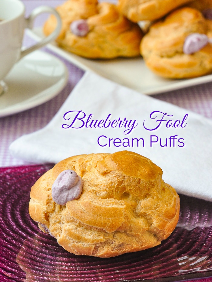 One Blueberry Fool Cream Puffs photop pf pne cream puff on a purple glass plate with text added for Pinterest
