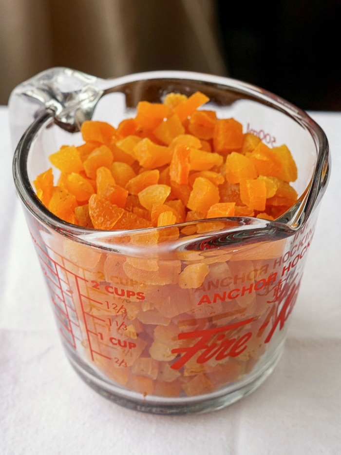 Chopped dried apricots in a clear measuring cup