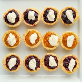 Close up overhead photo of Jam tarts with topped with cream