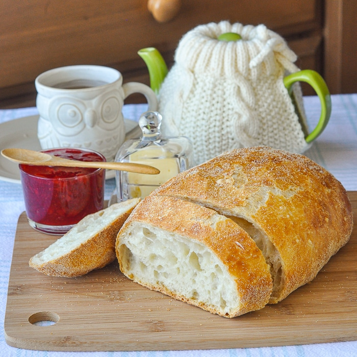 No knead Bread on a wooden cutting board with butter, jam and tea in the background